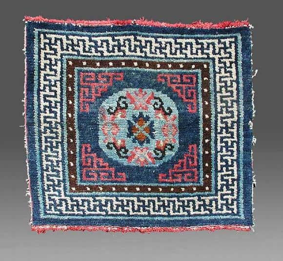 An early square mat with secular colours. The central medallion is related to those motifs seen in E. Turkestan rugs.