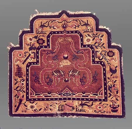An unusual and graphic example of pictorial art in a Tibetan weaving. The outline of the dragons bodies forms a goddess image with the jewel symbolizing a child moving through the birth canal.