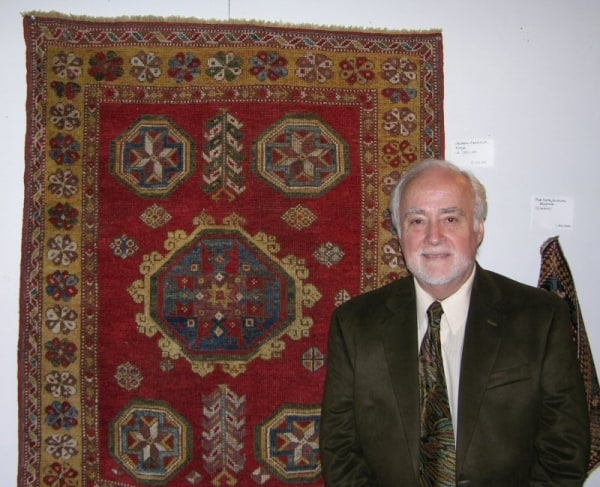 Dennis Dodds beside a Central Anatolian Konya rug from 1700-1725.