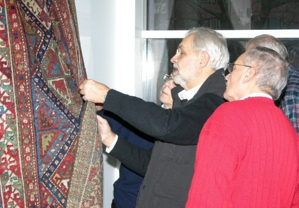 Søren Nissen, chairman of the Danish Rug Society, and Leif Schneidermann (right) are inspecting a rug.