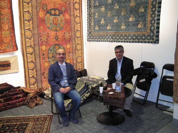 Rahim Farmand (left) in his stand with a Danish visitor Aram Safaei.