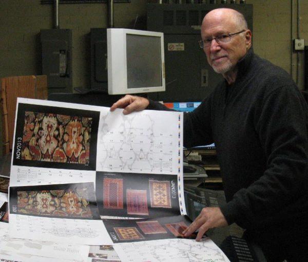 "Paul Shaper checking the print of their ""Woven Treasures 2013"" calendar"