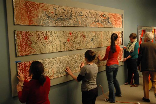 TM staff and interns work together to mount a batik triptych by American artist Vernal Bogren Swift. Photographer Katy Clune