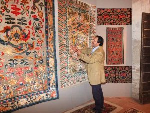 Farzin Mollaian in front of a Chinese silk carpet from the Forbidden City