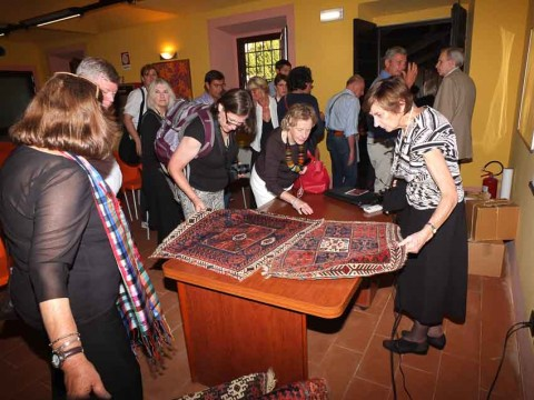Members of Stefano Ionescu's travel group inspecting some Balouch bags after DeWitt Mallary's lecture